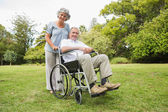 Happy mature man in wheelchair with partner — Stock Photo