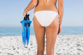Perfect feminine buttocks of young woman holding fins — Stock Photo