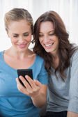 Smiling friends reading message on their phone — Stock Photo