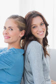 Happy women back against back and looking at camera — Stock Photo