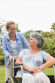 Cheerful mature woman in wheelchair talking with daughter — Stock Photo