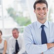 Cheerful businessman posing while his colleagues are working — Stock Photo #29450303