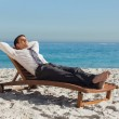 Young businessman relaxing on a deck chair — Stock Photo