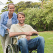 Happy man in wheelchair with partner — Stock Photo