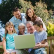 Smiling multi generation family with a laptop sitting in park — Stock Photo #29450579