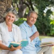 Happy older couple reading books together sitting on tree trunk — Stock Photo