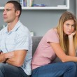 Couple sitting back to back after a fight on the couch with woma — Stock Photo