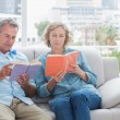Content couple reading books on the couch — Stock Photo