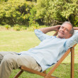 Happy mature msitting on sun lounger — Stock Photo #29451019