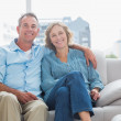 Happy couple relaxing on their couch — Stock Photo #29451069