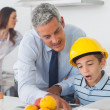 Father showing son his blueprints as he is wearing hardhat — Stock Photo #29451227