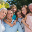 Smiling family and grandparents in the countryside embracing — Stock Photo #29451235