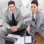 sorridente di colleghi di lavoro insieme seduti sul divano e utilizzando la — Foto Stock