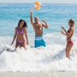 Happy friends playing with a beachball in the sea — Stock Photo