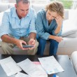 Middle aged couple sitting on their couch paying their bills — Stock Photo
