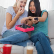 Stock Photo: Friends laughing at tv and sharing box of chocolates