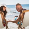 Cute couple looking at camera while lying on their deck chairs — Stock Photo