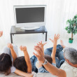 Family raising their arms in front of television — Stok fotoğraf