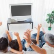Family raising their arms in front of television — ストック写真