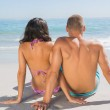 Pretty young couple sitting while looking at the sea — Stock Photo