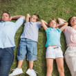 Sleeping family lying on the grass in a row — Stock Photo