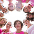 Group of happy women in circle wearing pink for breast cancer — Stock Photo