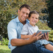 Happy dad and son with a tablet pc — Stock Photo #29452087