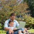 Stock Photo: Cheerful dad and son with a laptop