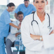 Serious blond doctor posing with colleagues in background — Stock Photo