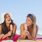 fröhlich hübsche Frauen liegen auf ihrem Handtuch Eis essen — Stockfoto