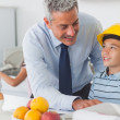 Father showing son his blueprints as he is wearing yellow helmet — Stock Photo