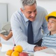Father showing son his blueprints as he is wearing yellow helmet — Stock Photo #29452323