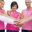 Stock Photo: Cheerful women posing in circle holding hands wearing pink for b