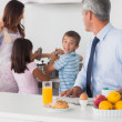 Father looking at his family cooking in the kitchen — Stock Photo #29452407