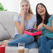 Stock Photo: Friends laughing and sharing box of chocolates
