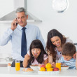 Father calling with mobile phone with his family eating breakfas — Stock Photo #29452937
