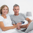Happy couple using their laptop to buy online — Stock Photo