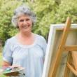 Happy mature woman painting on canvas — Stock Photo