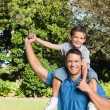 Son sitting on his fathers shoulders — Stock Photo
