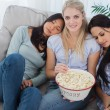 Friends dozing on blonde friends shoulders eating popcorn — Stock Photo