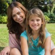 Smiling mother and daughter on the grass — Stock Photo