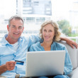 Cheerful couple sitting on their couch using the laptop — Stock Photo