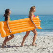 Two pretty friends running holding air mattress — Stock Photo