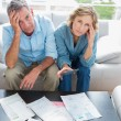 Anxious couple sitting on their couch paying their bills — Stock Photo #29453949