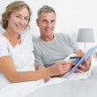 Happy couple using their tablet pc to buy online — Stock Photo #29453951