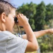 Boy looking through binoculars and pointing — Stock Photo