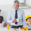 Funny little boy wearing fathers hardhat during breakfast — Stock Photo #29454011