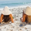 Attractive blonde and brunette in bikinis lying on the sand — Photo