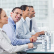 Stock Photo: Businessman smiling at camera while his colleagues listening to