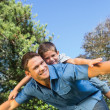 Son lying on his fathers back — Stock Photo